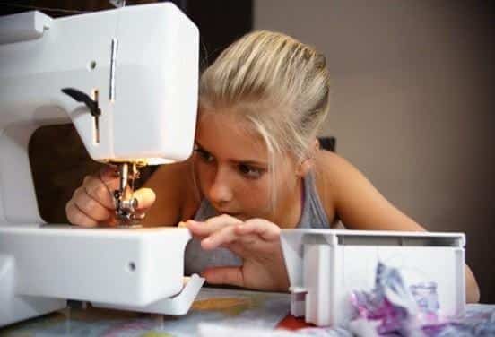Girl (10-12) with sewing machine --- Image by © Edvard March/Corbis